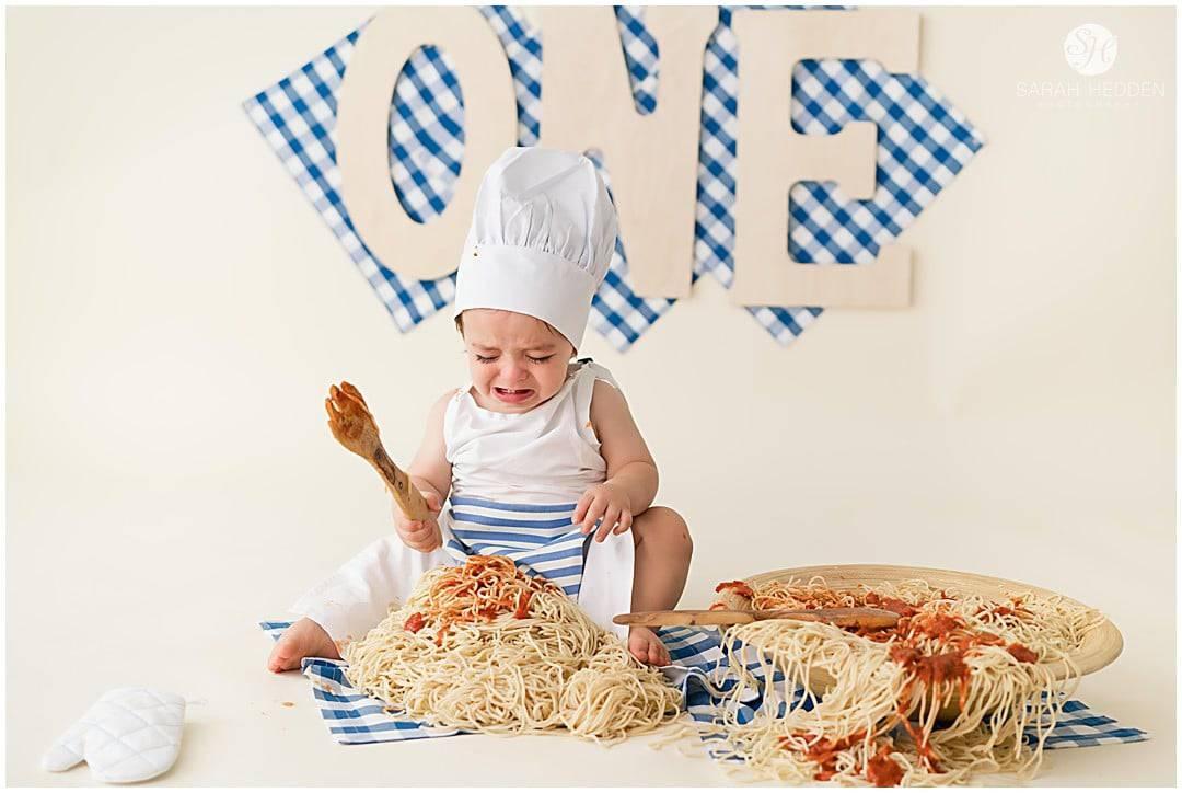 Little boy crying during his cake smash spaghetti smash session.