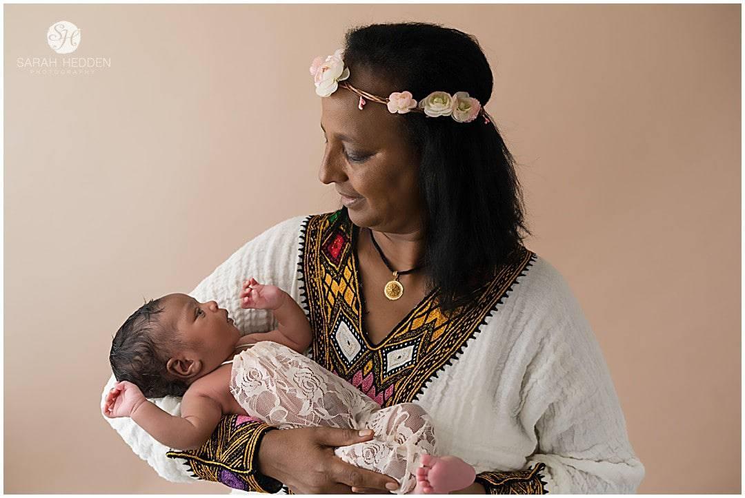 Grandma poses with grand baby girl during Milina's Newborn Baby Photos