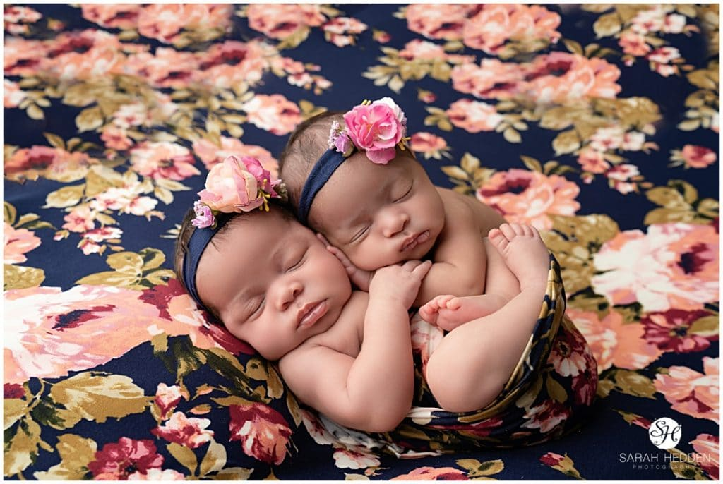 Twin girls posing on flower blanket with Jacksonville Newborn Photographer