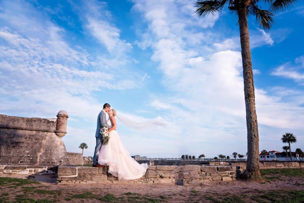 Bride and groom posing at Castillo de San Marcos at Alexis and Evan's White Room Wedding