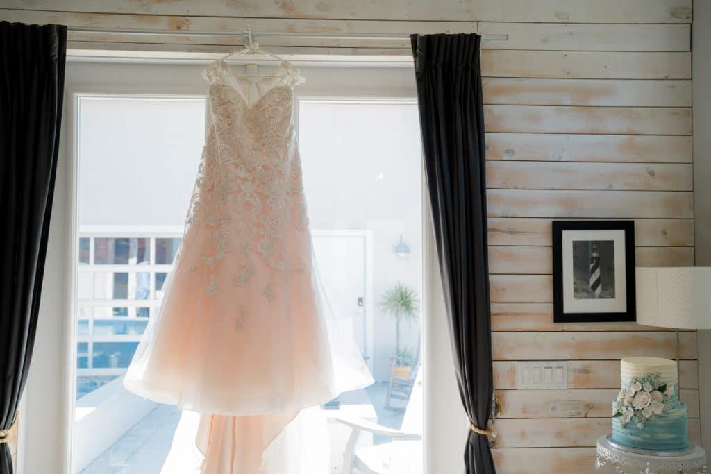 Wedding dress hanging in window at Tonya and Jon's Washington Oaks State Park Wedding
