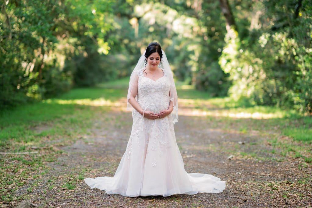 Bride posing holding her pregnant belly at Tonya and Jon's Washington Oaks State Park Wedding