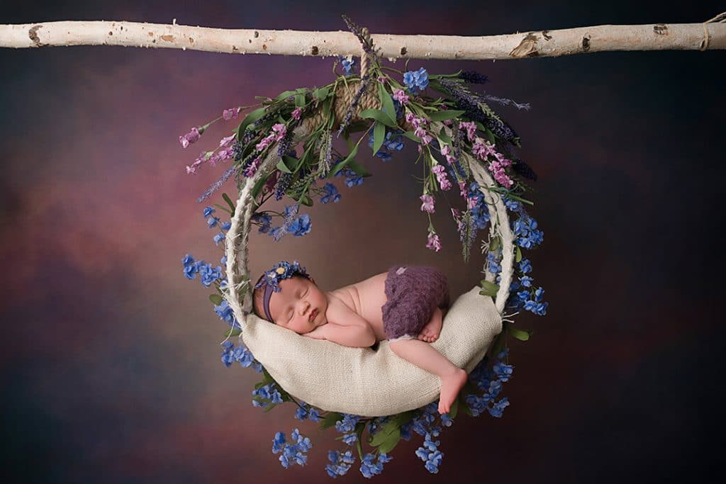 Baby girl in swing with purple backdrop with Jacksonville Newborn Photographer