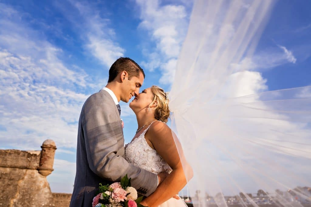 Bride and groom almost kissing with veil flying and blue skies in st. augustine.