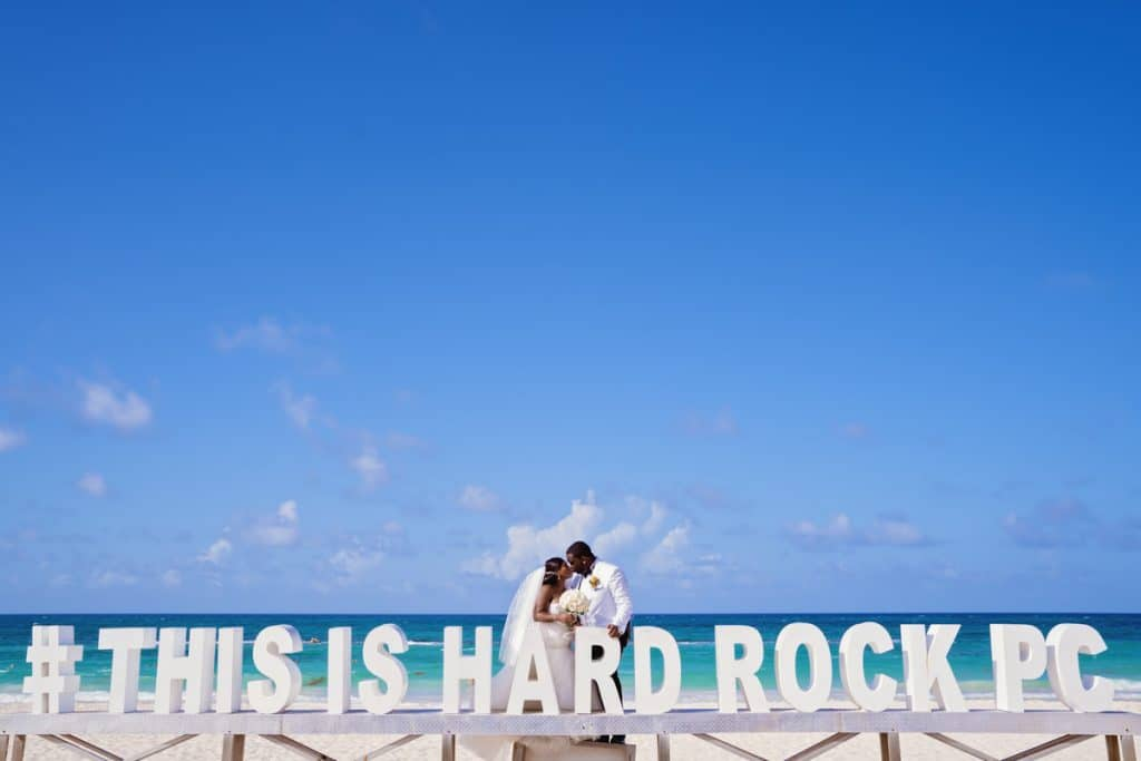 Bride and Groom pose at Hard Rock Sign at Shadai and Mo's Hard Rock Punta Cana Destination Wedding