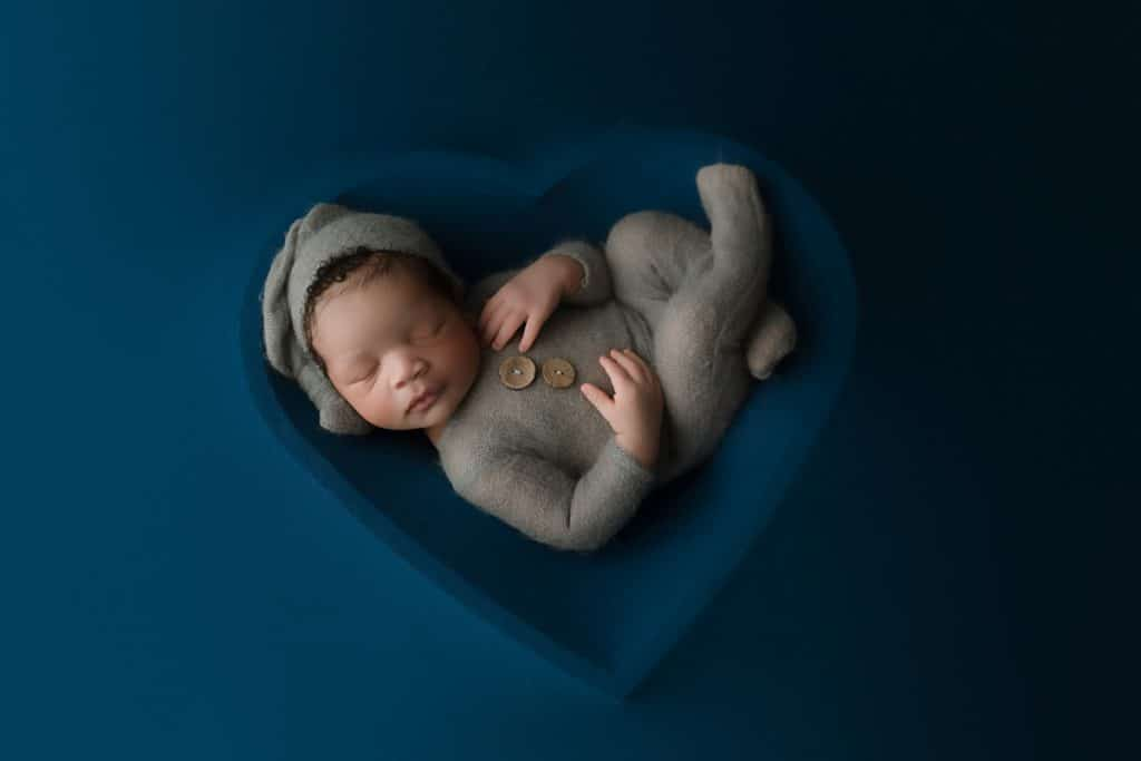 Newborn baby in heart bowl on blue sheet at Jacksonville newborn photographer