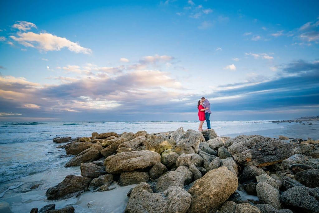 Couple kissing on rocks at beach with Jacksonville's best Engagement Photographer.