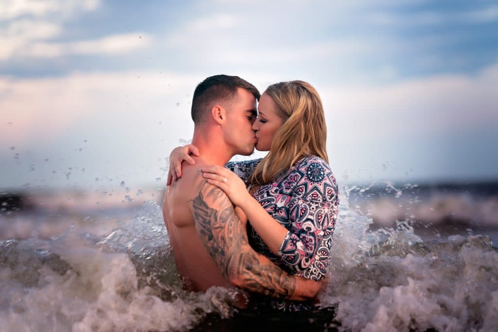Couple kissing in water at beach with Jacksonville's best Engagement Photographer.