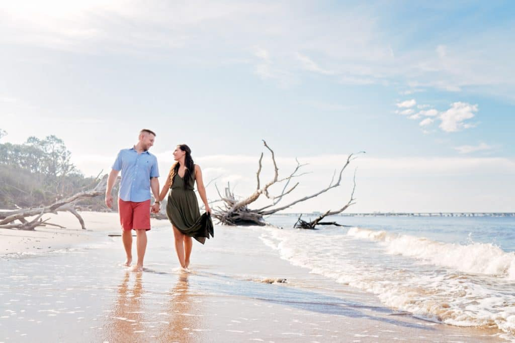 Couple walking on beach with Jacksonville's best Engagement Photographer.
