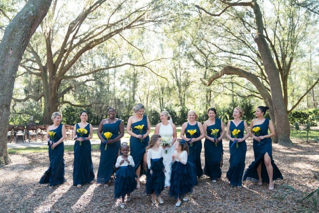 Bride walking with bridesmaids at Amber and Garvey's wedding at Bowing Oaks.