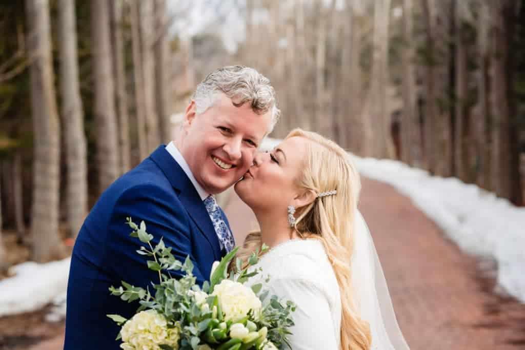 Bride kissing groom on the cheek at Heather and Jelmer's Utah Wedding