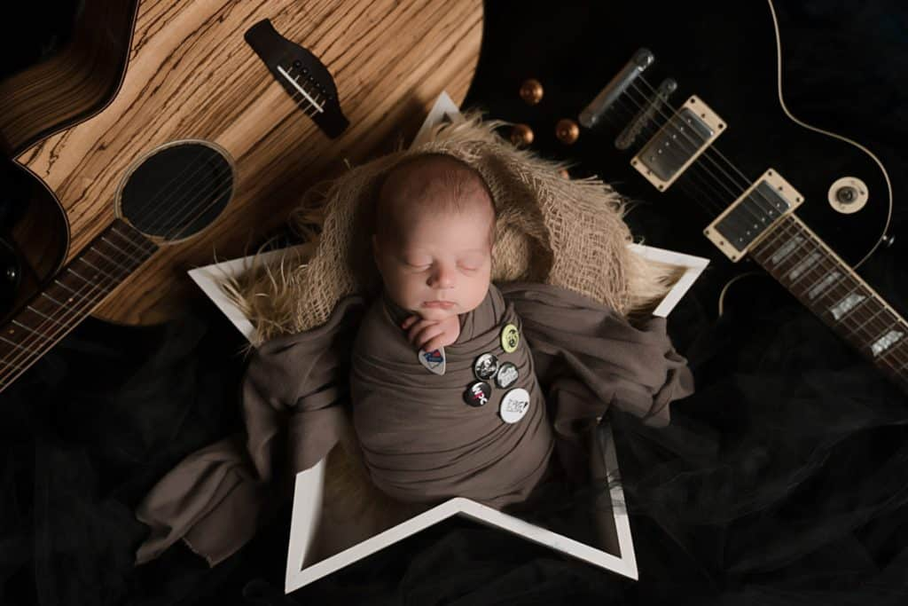 Newborn boy wrapped in star prop with guitars surrounds at his outdoor newborn session.