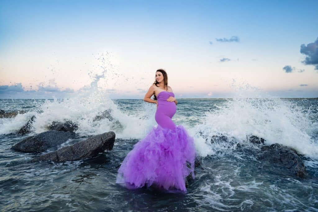 Pregnant mama in purple mermaid tulle dress on rocks with beach waves crashing behind her