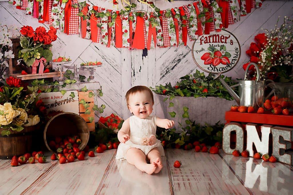 Cake smash with strawberries all around baby.