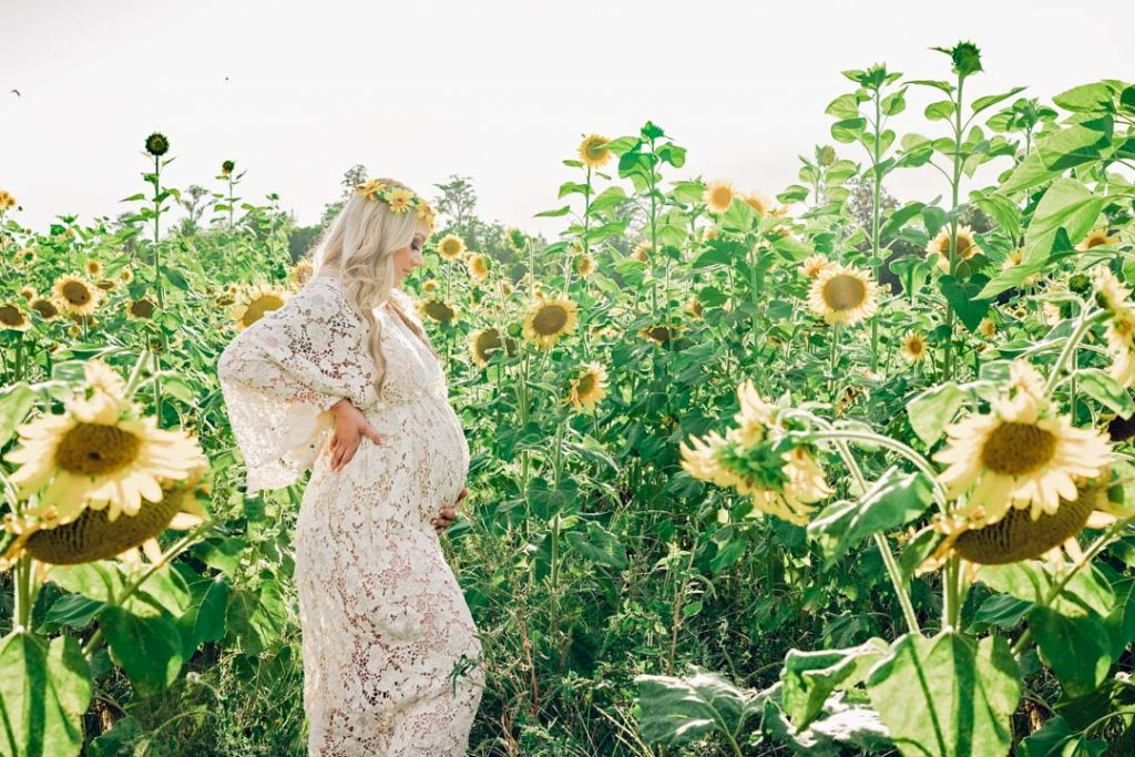 Pregnant mama in sunflower field in maternity dress at sunset at her maternity session in jacksonville