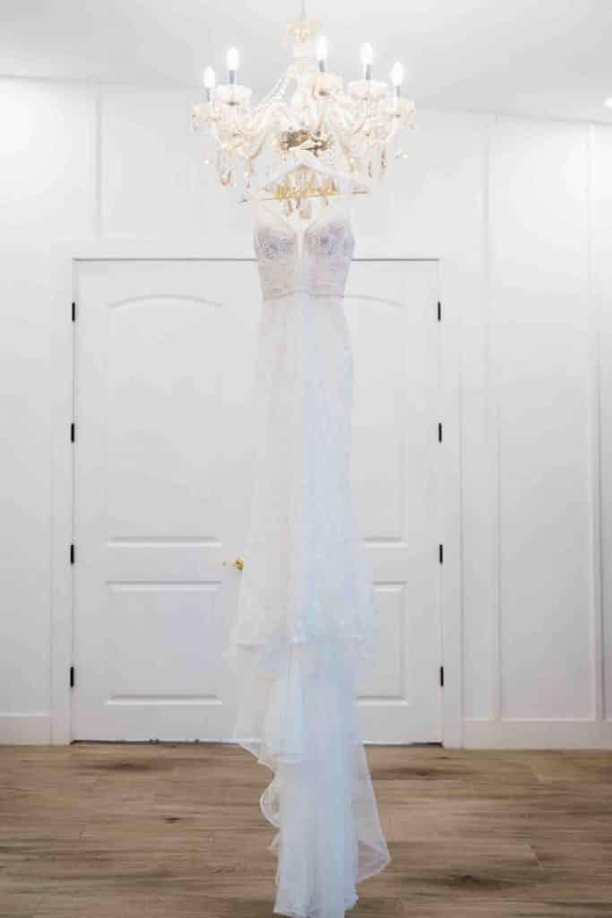 Wedding dress hanging on chandelier at Brooke and Josh's New Smyrna Beach Wedding
