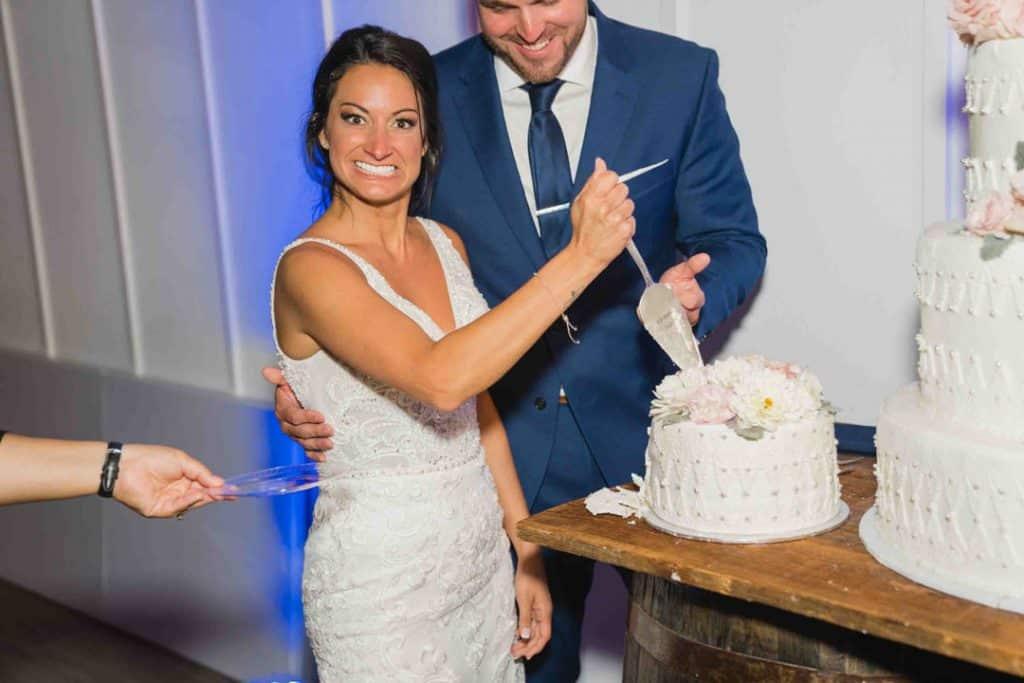 bRide stabbing cake at Brooke and Josh's New Smyrna Beach Wedding