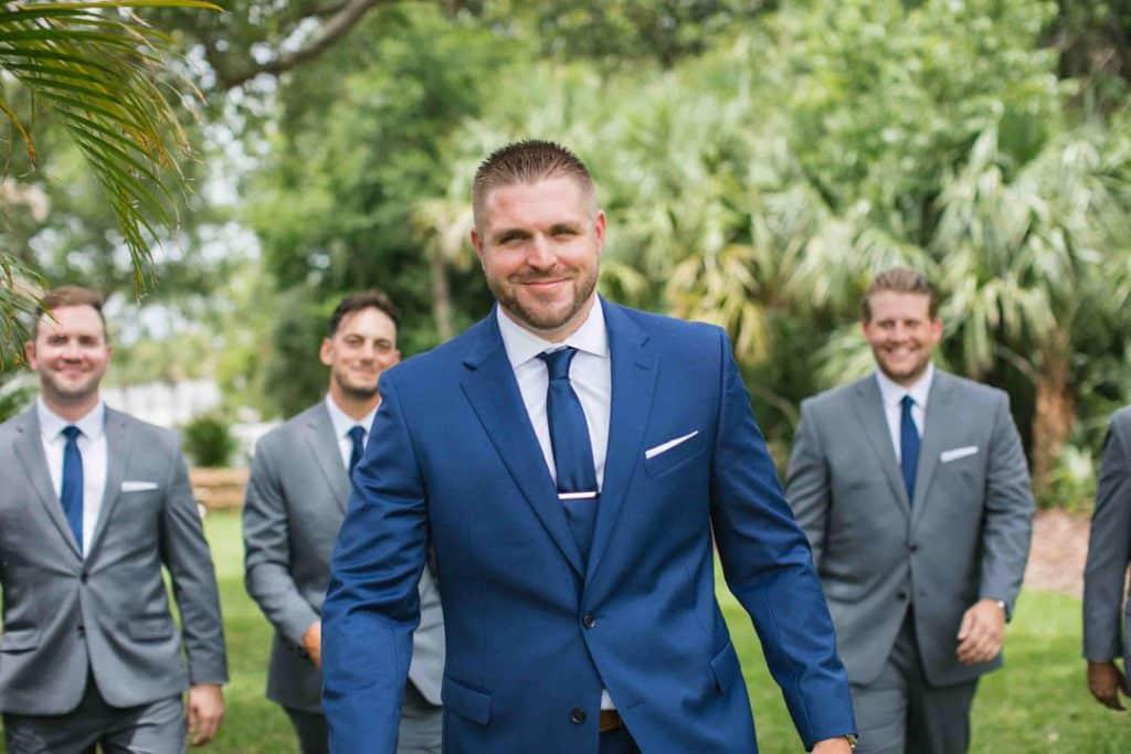 Groom walking with his groomsmen behind him at Brooke and Josh's New Smyrna Beach Wedding