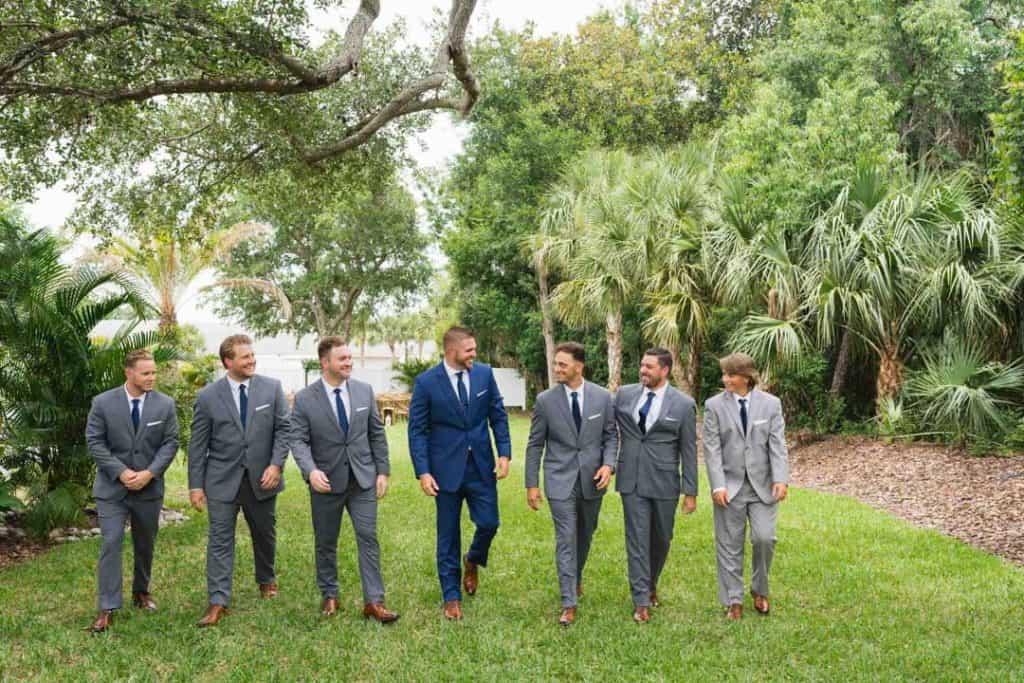 Groom walking with his groomsmen at Brooke and Josh's New Smyrna Beach Wedding