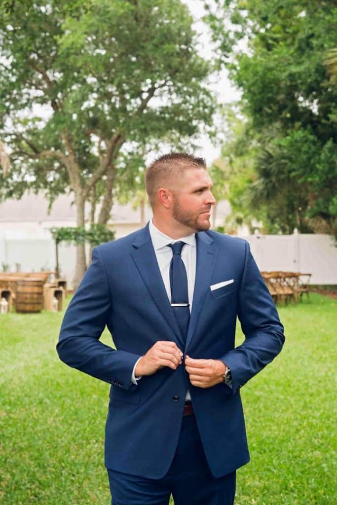 Groom posing buttoning his jacket at Brooke and Josh's New Smyrna Beach Wedding